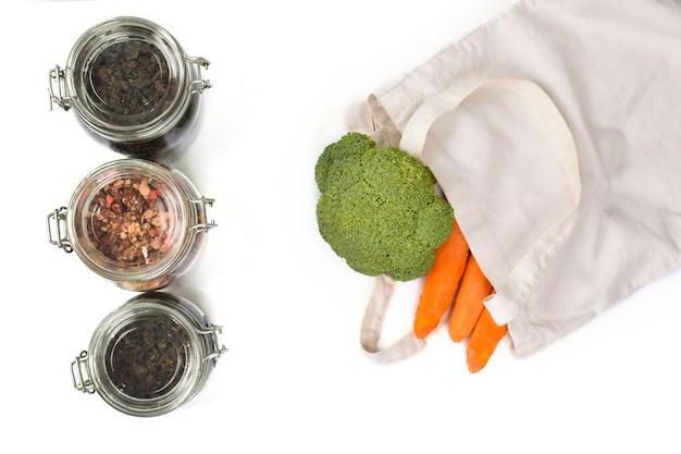 Świeże warzywa w ekologicznej beżowej torbie na białej ścianie. koncepcja zero waste. skopiuj miejsce, płasko.