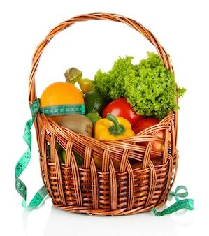 Świeże warzywa w wiklinowym koszu na białym tle