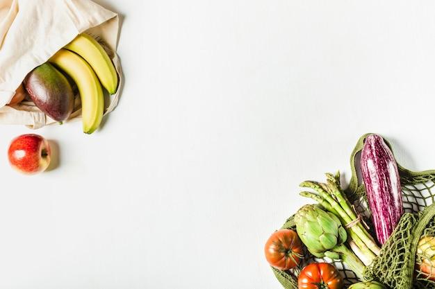 Świeże warzywa w zielonej torebce sznurkowej i owocach w torebce wykonanej z naturalnych materiałów