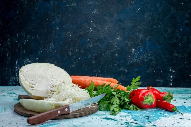 Świeże warzywa warzywa pokrojone w plasterki kapusta marchew i ostra ostra papryka na jasnoniebieskim biurku, jedzenie posiłek warzywny obiad zdrowa sałatka