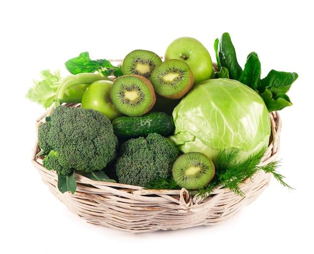 Świeże warzywa z liśćmi - brokuły, kiwi, seler, szpinak, jarmuż, winogrona i jabłko na białym tle