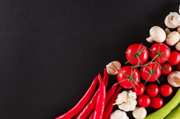Świeże warzywa z miejsca kopiowania dla zdrowego gotowania lub robienia sałatek na czarnej powierzchni
