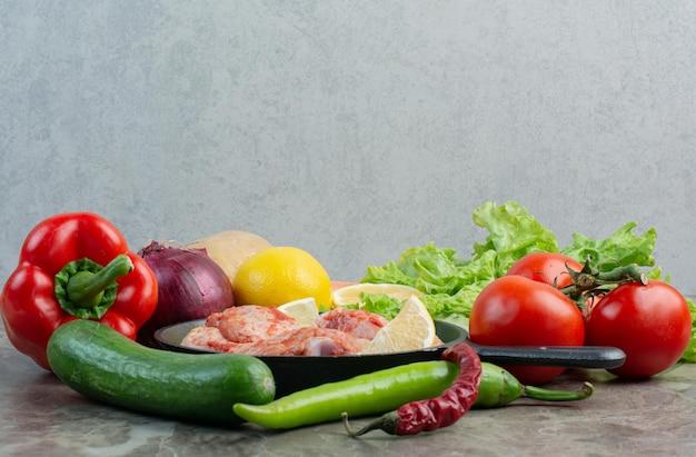 Świeże warzywa z surowym kurczakiem na marmurowym tle. zdjęcie wysokiej jakości