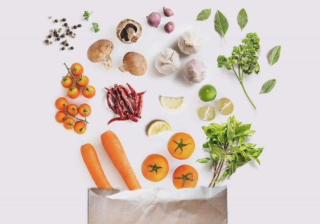 Świeże warzywa z ziołami i przyprawami rozlane z papierowej torby na zakupy