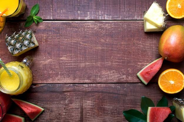 Świeże wielo- owoc i smoothie na ciemnym drewnianym nieociosanym tle, mieszkanie nieatutowej i kopii przestrzeni