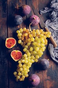 Świeże winogrona i figi na starej drewnianej powierzchni w stylu retro
