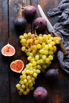 Świeże winogrona i figi na starym drewnianym tle w stylu retro. widok z góry