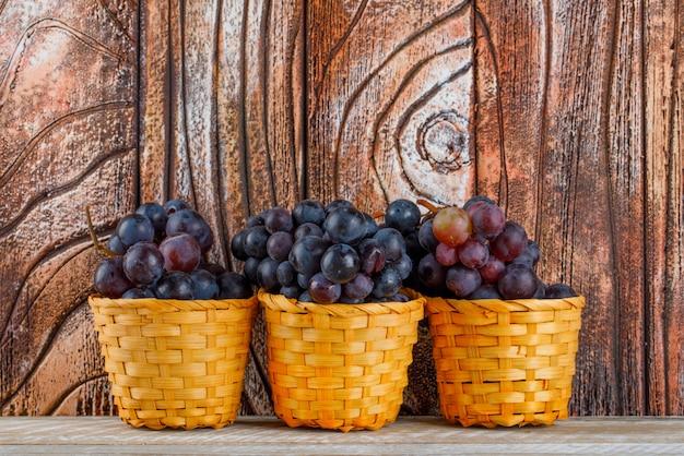 Świeże winogrona w wiklinowych koszach na podłoże drewniane, widok z boku.