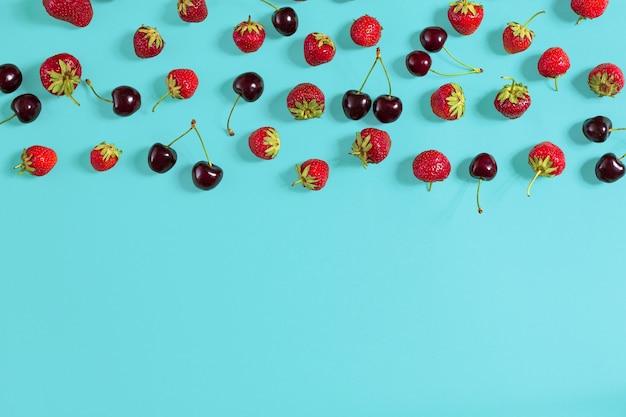 Świeże wiśnie i truskawki na tle mięty, widok z góry. skopiuj miejsce. martwa natura makieta płaska leżała