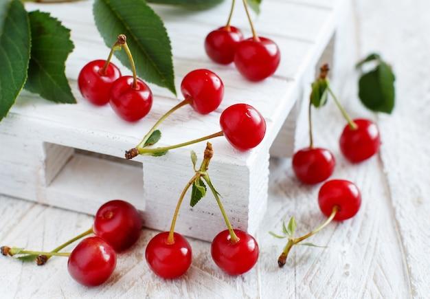 Świeże wiśnie na białym drewnianym stole