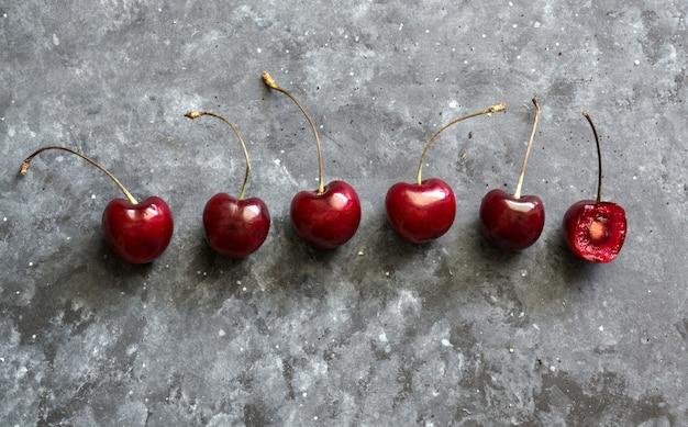 Świeże wiśnie na czarnym tle. wzór owoców.