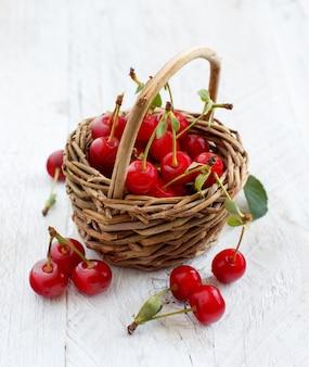 Świeże wiśnie w koszu na drewnianym stole