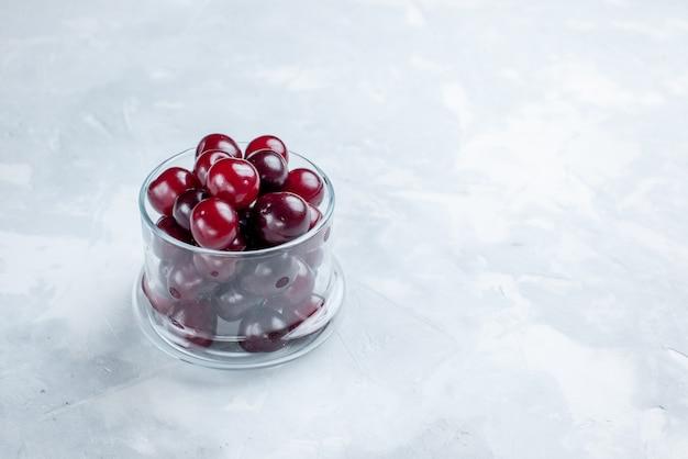 Świeże wiśnie w małym szklanym kubku na biurku z białym światłem, zdjęcie z kwaśną witaminą owocową