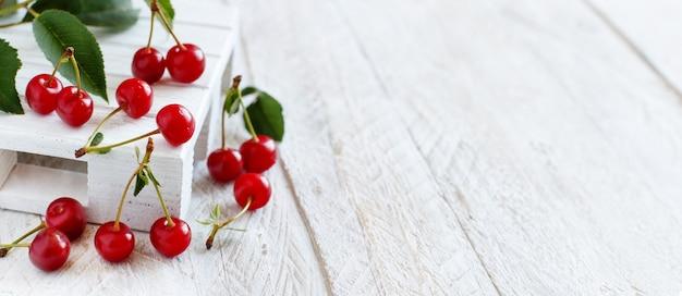 Świeże wiśnie z liśćmi na białym drewnianym stole