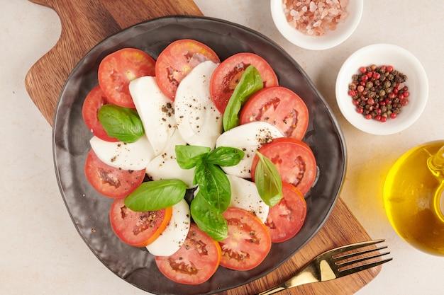 Świeże włoskie antipasto sałatkowe caprese z mozzarellą bawolą, plastrami pomidorów i bazylią z oliwą z oliwek. składniki na wegetariańską sałatkę caprese. włoskie jedzenie. widok z góry. styl rustykalny.