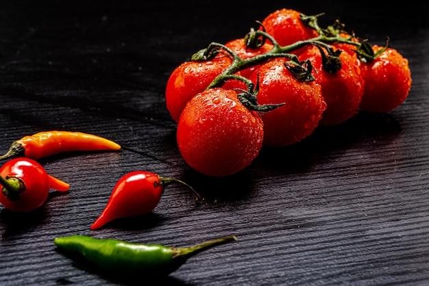 Świeże włoskie pomidory na czarnym rustykalnym drewnianym stole z kilkoma papryczkami wokół nich na drewnianym stole. widok z góry