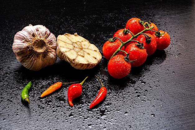 Świeże włoskie pomidory na czarnym rustykalnym drewnianym stole z kilkoma paprykami i czosnkiem pokrojonym na pół wokół, na drewnianym stole.