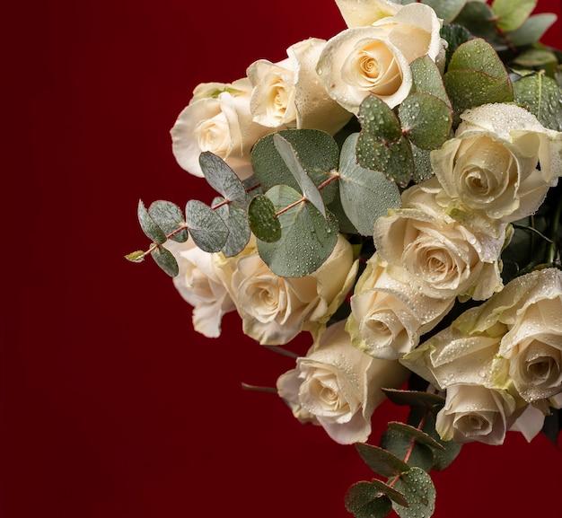 Świeże, wspaniałe kwiaty z kroplami wody i gałęziami drzewa eukaliptusowego