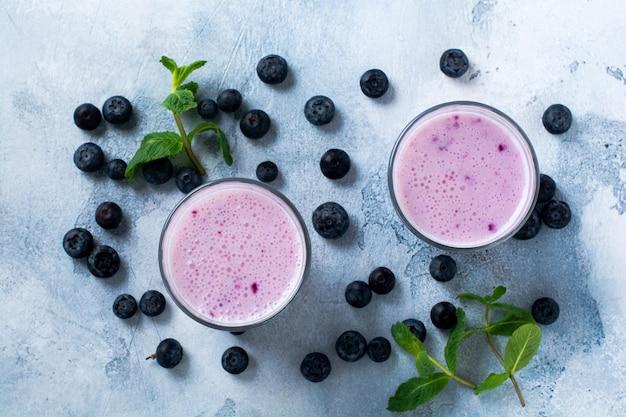 Świeże zdrowe jagody smoothie jagody i mięta w szkle na jasnobiałej powierzchni betonu