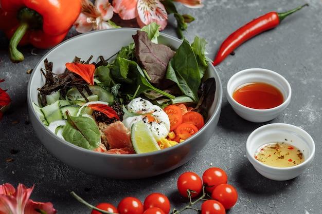 Świeże, zdrowe, lekkie śniadanie, lunch biznesowy. śniadanie z jajkiem w koszulce, kaszą gryczaną, czerwoną rybą, świeżą sałatą