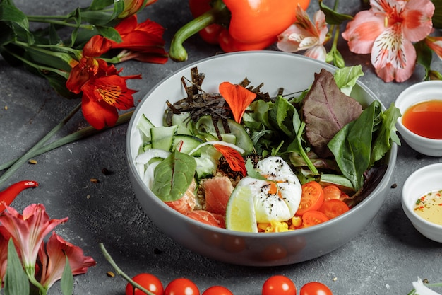 Świeże zdrowe lekkie śniadanie, lunch biznesowy. śniadanie z jajkiem w koszulce, kaszą gryczaną, czerwoną rybą, świeżą sałatką, ogórkami i pomidorami koktajlowymi, koncepcja lunchu biznesowego