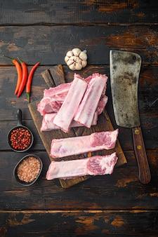 Świeże żeberka wieprzowe doprawione zestawem przypraw, ze starym nożem rzeźniczym, na starym ciemnym drewnianym stole
