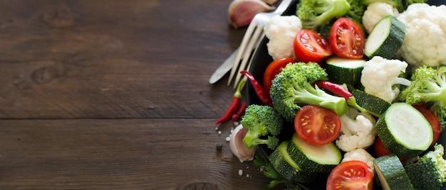 Świeże zielone brokuły i warzywa na drewnianym stole