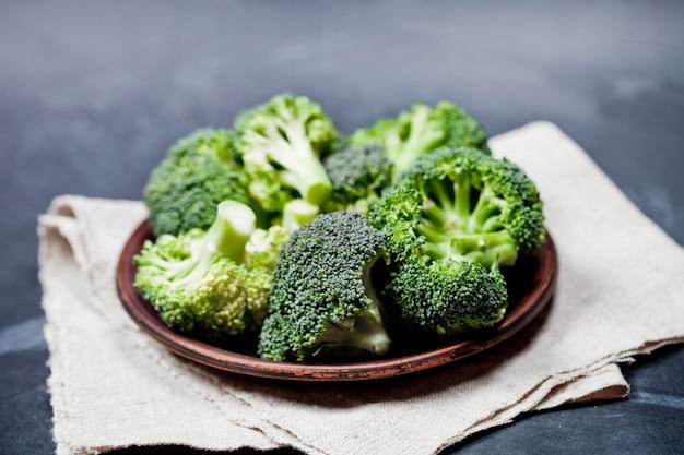 Świeże zielone brokuły organiczne w brązowy talerz i serwetka lniana