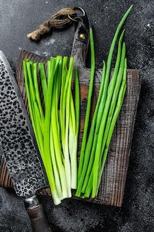 Świeże zielone cebule na desce do krojenia. czarne tło. widok z góry.