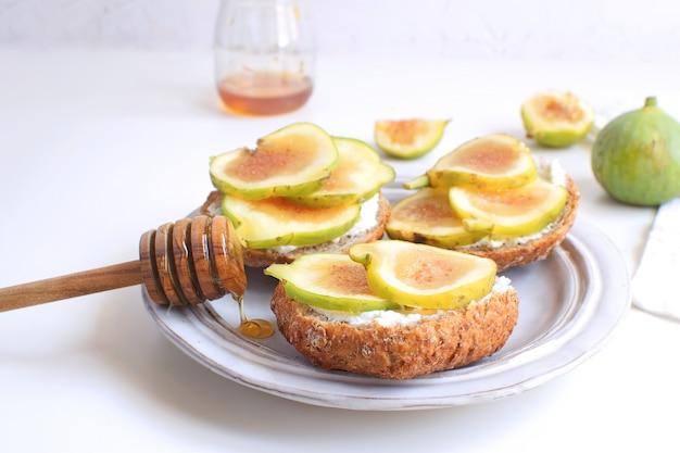 Świeże zielone figi porcelanowy talerz pełnoziarnisty chleb miód ser kozi