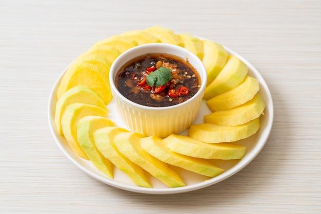 Świeże zielone i złociste mango z maczaniem w słodkim sosie rybnym - styl azjatycki