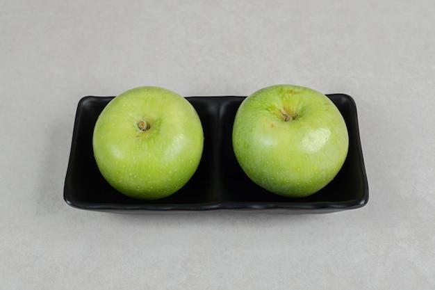 Świeże zielone jabłka na czarnej płycie