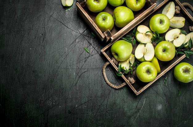 Świeże zielone jabłka na drewnianej tacy. na rustykalnym tle.