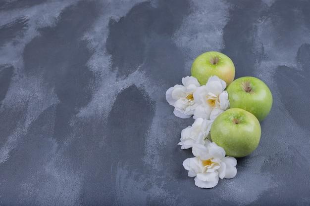 Świeże zielone jabłka na niebieskiej powierzchni z kwiatami.