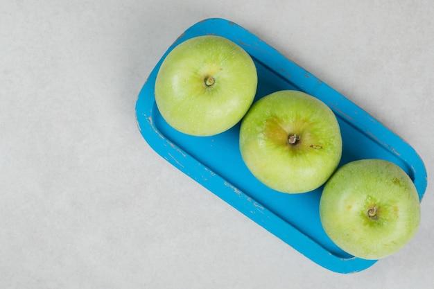 Świeże zielone jabłka na niebieskim talerzu