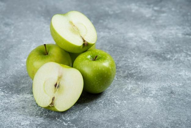 Świeże zielone jabłka na tle marmuru.
