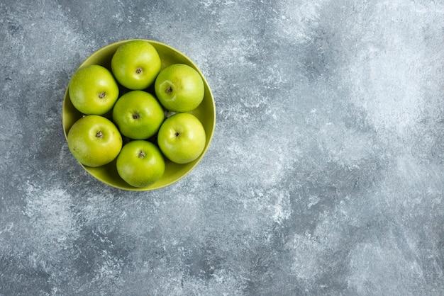 Świeże zielone jabłka na zielonym talerzu