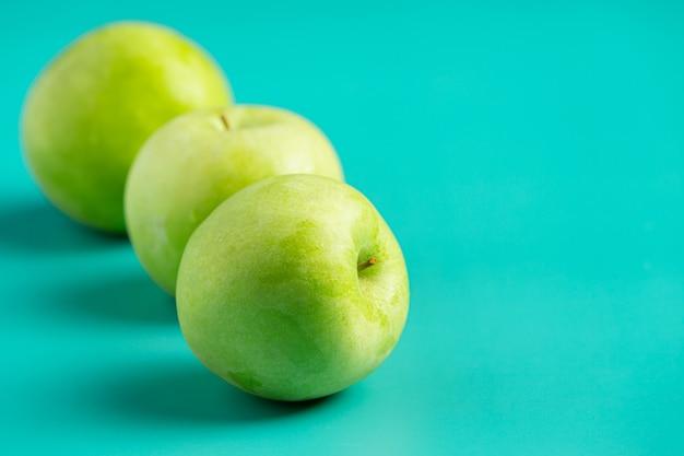 Świeże zielone jabłka umieścić na jasnozielonym tle