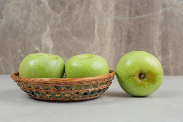 Świeże zielone jabłka w drewnianym koszu.