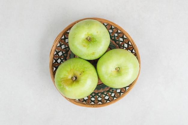 Świeże zielone jabłka w drewnianym koszu