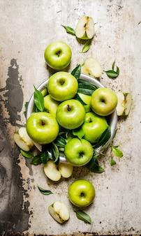 Świeże zielone jabłka w naczyniu na rustykalnym tle. widok z góry