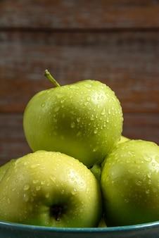 Świeże zielone jabłka z kroplami wody na nich
