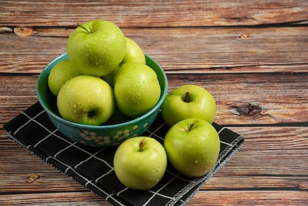 Świeże zielone jabłka z kropli wody na nich w niebieskiej misce, widok z góry