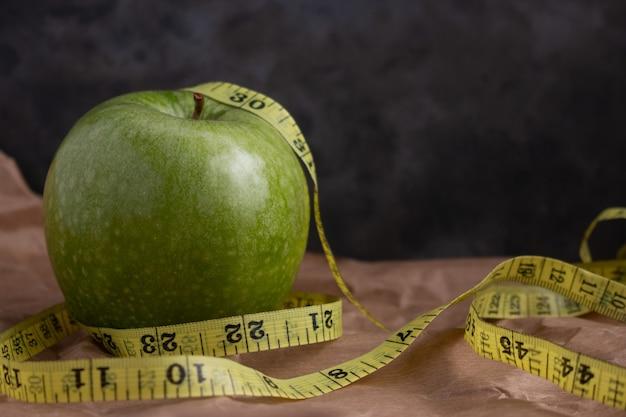 Świeże zielone jabłko i centymetrowa taśma