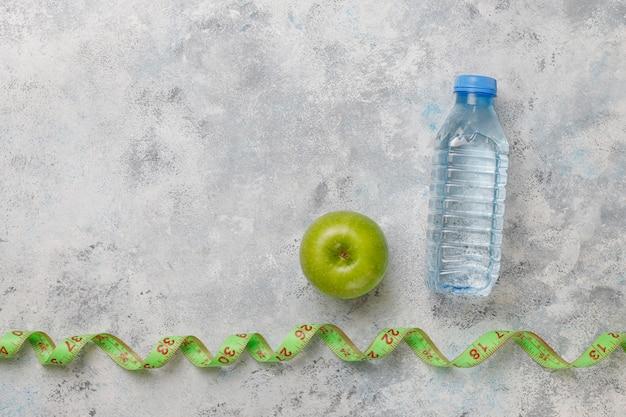 Świeże zielone jabłko, miara taśmy i butelka świeżej wody na szarym betonie