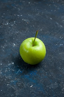 Świeże zielone jabłko na białym tle na ciemnym biurku
