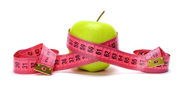 Świeże zielone jabłko z czerwoną miarą na białym tle. koncepcja żywności dieta.