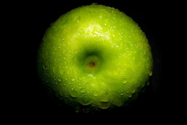 Świeże zielone jabłko z kroplami wody na czarnym tle