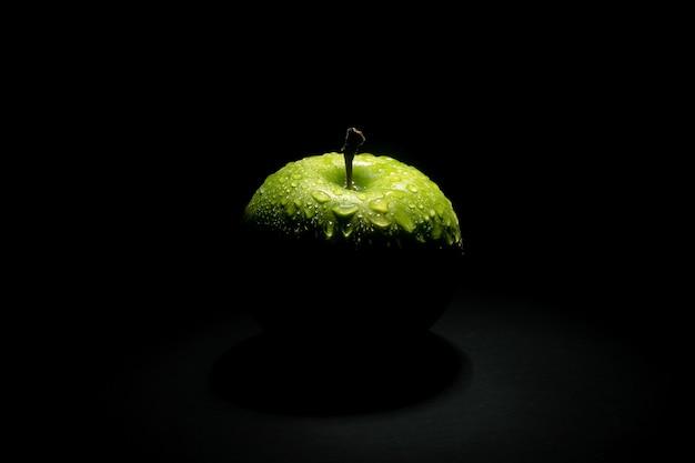 Świeże zielone jabłko z kropli wody na ciemnym tle