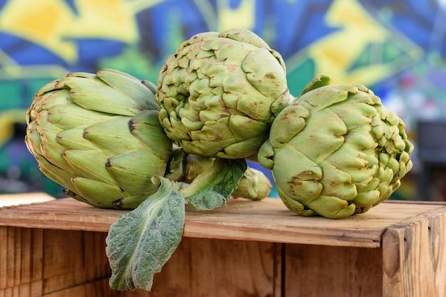 Świeże zielone karczochy śródziemnomorskie na drewnianym pudełku na sprzedaż na jeden urlop na rynku.